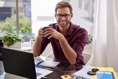 Junger haltener Berufskaffee und Lächeln an seinem Schreibtisch Stockfotos