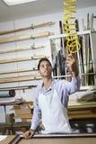 Junger Handwerker, der Ausrüstung in der Rahmenwerkstatt hält Lizenzfreie Stockfotografie