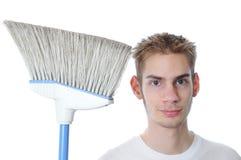 Junger Hausmeister, der mit Besen lächelt Stockfoto