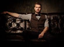 Junger hübscher altmodischer bärtiger Mann, der auf bequemem ledernem Sofa auf dunklem Hintergrund sitzt Stockbild