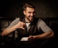 Junger hübscher altmodischer bärtiger Mann, der Spaß mit Tasse Kaffee auf bequemem ledernem Sofa auf dunklem Hintergrund hat Lizenzfreies Stockfoto