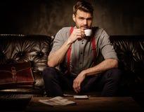 Junger hübscher altmodischer bärtiger Mann mit dem Tasse Kaffee, der auf bequemem ledernem Sofa auf dunklem Hintergrund sitzt Stockbilder