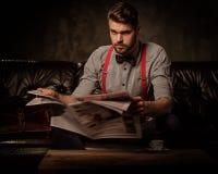 Junger hübscher altmodischer bärtiger Mann mit der Zeitung, die auf bequemem ledernem Sofa auf dunklem Hintergrund sitzt Stockbild