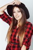 Junger hübscher Brunettemädchenhippie im Hut auf zufälligem Abschluss des weißen Hintergrundes das Lächeln oben träumend wirklich Stockfotografie
