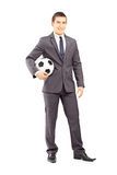 Junger hübscher Geschäftsmann, der einen Fußball hält Stockbilder