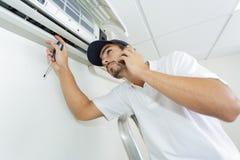 Junger Heimwerker, der die Klimaanlage ruft um Hilfe repariert stockfoto