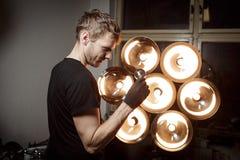 Junger heller Designer, der alte elektrische Birne betrachtet stockfoto