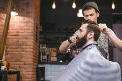 Junger Herrenfriseur, der einem bärtigen Mann den Haarschnitt der Männer macht stockfotos