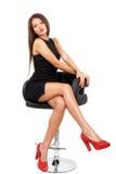 Junger herrlicher kaukasischer Brunette im schwarzen Kleid auf dem Stuhl Stockbild