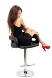 Junger herrlicher kaukasischer Brunette im schwarzen Kleid auf dem Stuhl Stockfoto