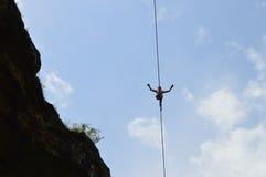 Junger highline Wanderer hoch auf einem Drahtseil im Himmel stockbild