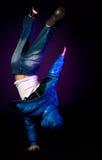Junger Hip-hoptänzer, der Akrobatik durchführt. Stockfoto