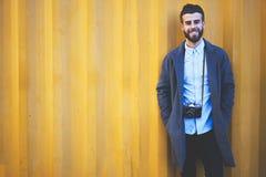 Junger Hippie Bloggerreisender in einer Denimjacke, die auf buntem Einstellungshintergrund für sein Blog während steht Stockfoto