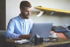 Junger Hippie Bloggerreisender, während das Mit Monotype setzen auf Laptop-Computer an Radioapparat 5G anschloss Lizenzfreie Stockfotos
