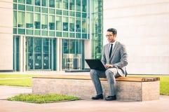 Junger Hippie-Geschäftsmann mit Laptop im Geschäftszentrum Stockfotos