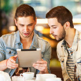 Junger Hippie-Kerl, der in einem Café plaudernden und trinkenden coffe sitzt Stockbilder