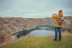 Junger Hippie-Kerl, der Foto auf seiner Handykamera von einem See macht Stockfotos