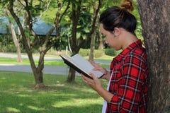 Junger Hippie-Mann, der einen Baum lehnt und ein Buch im Naturhintergrund liest Stockbild