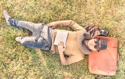 Junger Hippie-Mann, der sich mit einer Tablette in seinen Händen hinlegt Lizenzfreies Stockfoto