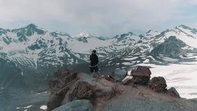 Junger Hippie-Mann des Luftschusses auf den Felsen, die in den schneebedeckten Bergen aufwerfen stock video footage