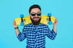 Junger Hippie-Mann mit einem Skateboard Lizenzfreie Stockbilder