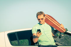 Junger Hippie-Mann mit hörender Musik des Smartphone während der Reise Stockbild