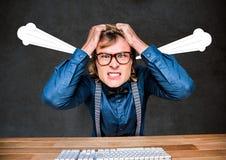 Junger Hippie-Mann verärgert, mit den Händen auf Kopf und Dampf auf Ohren Lizenzfreie Stockbilder