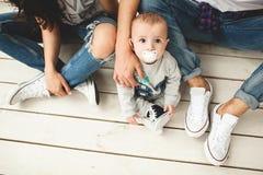 Junger Hippie-Vater, -mutter und -Baby auf Bretterboden Stockfotos
