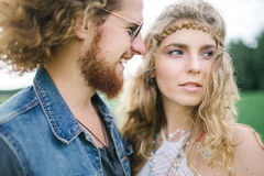 Junger Hippiemann mit dem Bart, der draußen gelockte Frau umarmt lizenzfreie stockfotografie