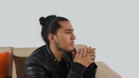 Junger hispanischer Mann mit dem erfassten Haar erfolgten Bogen, der schwarzes T-Shirt und schwarze Lederjacke trägt stockfoto
