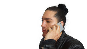 Junger hispanischer Mann mit dem Haar band oben getan im schwarzen Kleid und in der schwarzen Lederjacke, mit seinem Handy in sei stockfotos