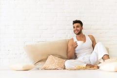 Junger hispanischer Mann Sit On Pillows Floor, glückliches lächelndes Guy With Breakfast Tray Look-Kopien-Raum-Schlafzimmer Lizenzfreies Stockbild