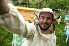 Junger Imker macht selfie im Bienenhaus Stockfotografie