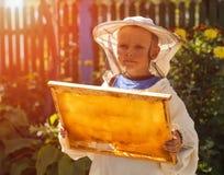 Junger Imkerjunge, der Rahmen der Bienenwabe hält Stockbilder