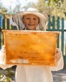 Junger Imkerjunge, der Rahmen der Bienenwabe hält Stockfoto