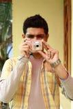 Junger indischer Mann, der Foto in der Digitalkamera nimmt Lizenzfreie Stockfotos