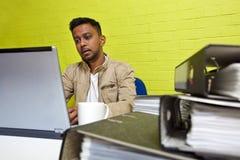 Junger indischer Mann, der an seinem Computer umgeben durch Ordner arbeitet stockfotos