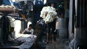 Junger indischer Mann, der Wäscherei vom Kanister in einer Manufaktur in Mumbai nimmt stock video footage