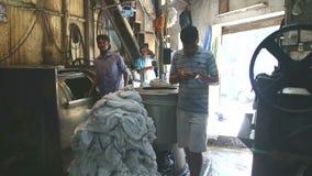 Junger indischer Mann, der Wäscherei vom Kanister in einer Manufaktur in Mumbai nimmt stock footage