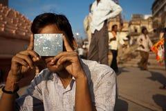 Junger indischer Mann sieht Eklipse mit Solarfilter an Stockfoto
