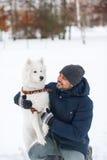 Junger indischer Mann und fester weißer flaumiger Hund am Wintertag Lizenzfreie Stockfotos