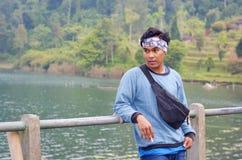Junger indonesischer Mann-rauchende Zigarette nah an dem See, Bali lizenzfreies stockbild
