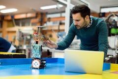 Junger Ingenieur, der seinen Roboter in der Werkstatt prüft Stockfoto