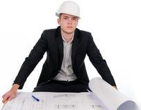 Junger Ingenieur mit dem Plan, der Kamera betrachtet Stockbild