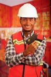 Junger Ingenieurtischler, der quadratisches Muster flanel Hemd mit der roten Sicherheitsweste, die Leimpistole halten trägt, die  Stockbilder