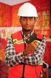 Junger Ingenieurtischler, der quadratisches Muster flanel Hemd mit der roten Sicherheitsweste, die Leimpistole halten trägt, die  Stockbild