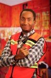 Junger Ingenieurtischler, der quadratisches Muster flanel Hemd mit der roten Sicherheitsweste, Handelektrowerkzeug halten trägt Stockfotos