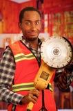 Junger Ingenieurtischler, der quadratisches Muster flanel Hemd mit der roten Sicherheitsweste, Handwerkzeug der elektrischen Sand Lizenzfreie Stockfotografie