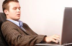 Junger intelligenter beiläufiger Geschäftsmann, der an Laptop arbeitet Stockfotos