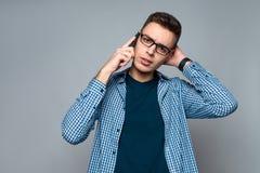 Junger intelligenter Kerl mit Gläsern spricht am Telefon stockfotos